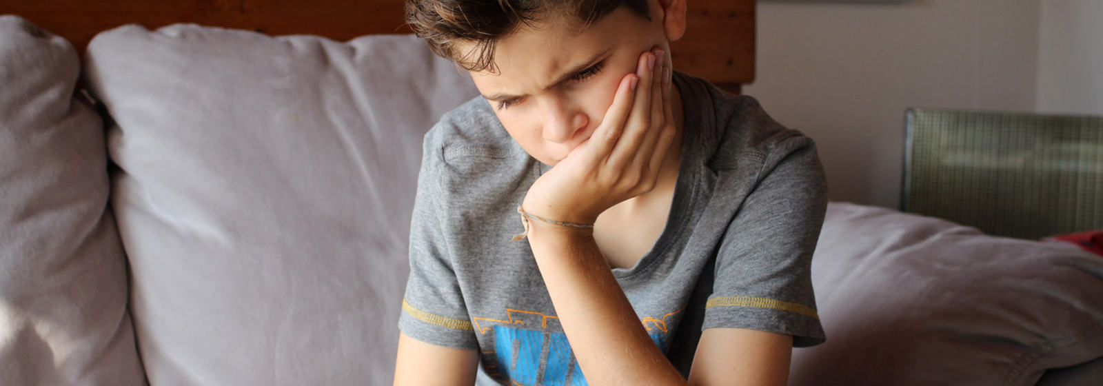Picture of boy with head resting in his hand looking sad